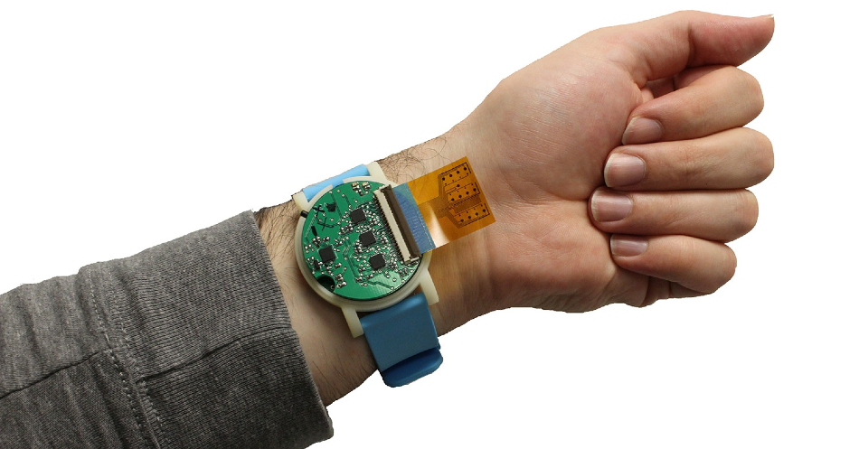 The metabolite monitoring device, shown here, is the size of a wristwatch. The sensor strip, which sticks out in this photo, can be tucked back, lying between the device and the user's skin